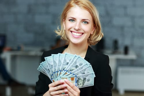 14-Day Interest Free Loan: Young woman smiling with cash