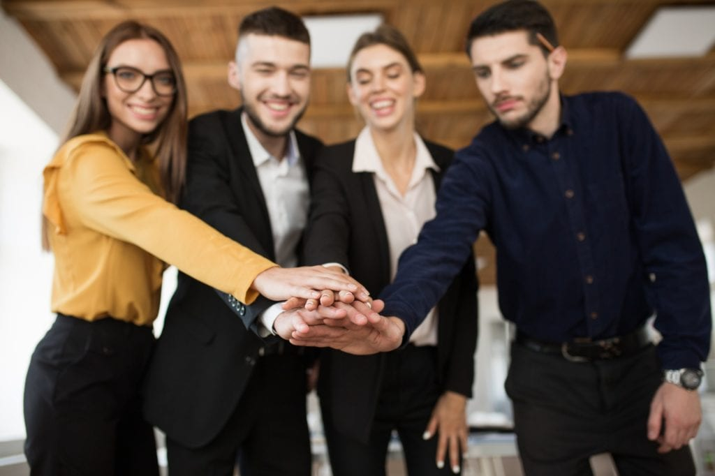 Group of smiling business partners in suits showing unity with t